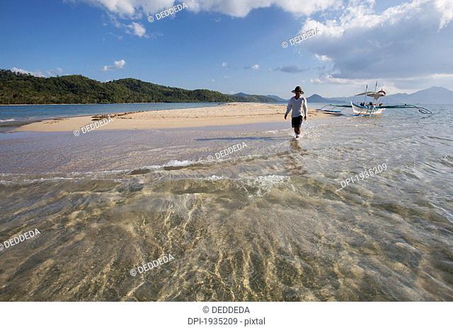 a male tourist walks along the white sand on a small island near el nido, bacuit archipelago, palawan, philippines