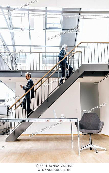 Businesswoman and businessman walking on stairs in a loft