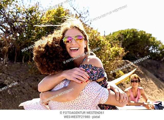 Happy couple hugging outdoors in summer