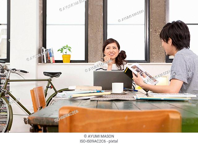Young couple in apartment sitting at table