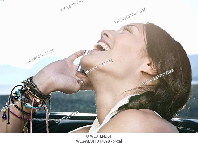 Spain, Majorca, Young woman using cell phone in car back seat, close up