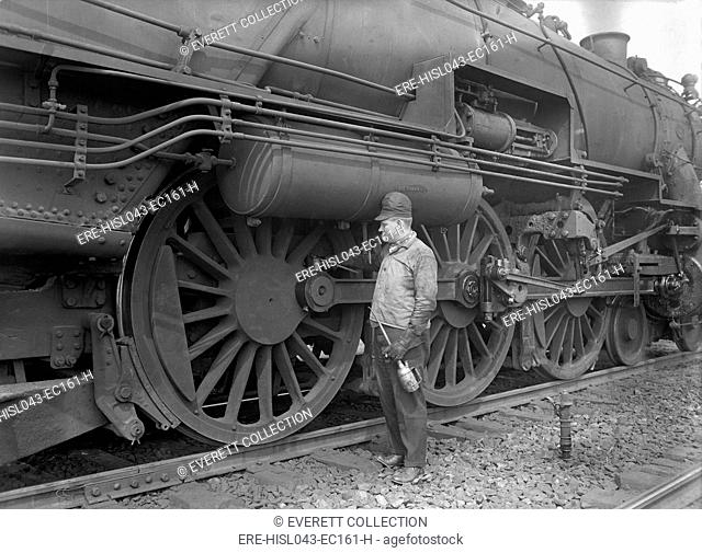 Mechanic servicing a railway steam engine in 1924. Massive locomotives has increased speed and power to move heavier loads (BSLOC-2016-10-178)