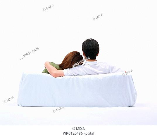 Rear view of a couple resting on couch