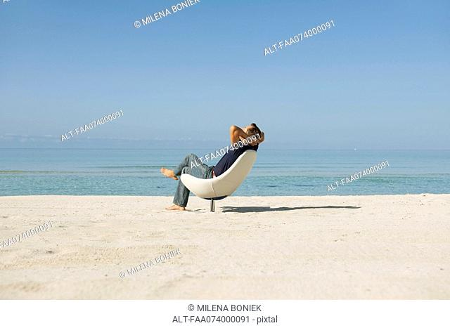 Mid-adult man relaxing in armchair on beach