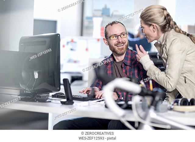 Woman talking to smiling colleague at desk in office
