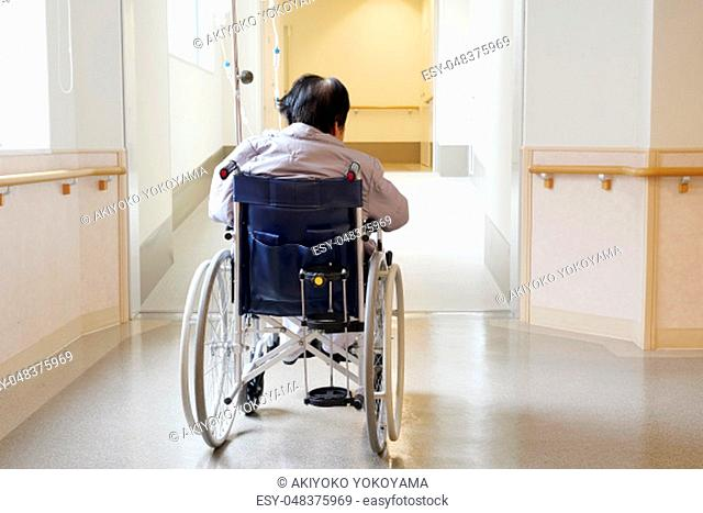 Back view of senior or elderly woman on wheelchair at hospital hallway