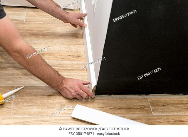 Close up of man fitting skirting board