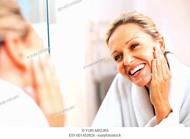 A happy beautiful mature woman admiring herself in the mirror
