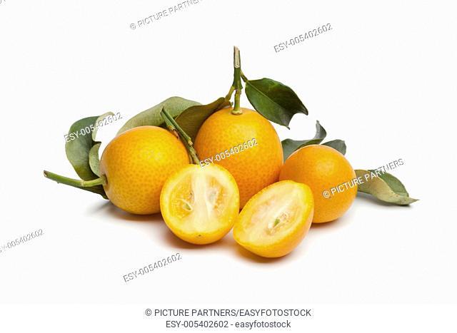 Fresh round half and whole kumquats on white background