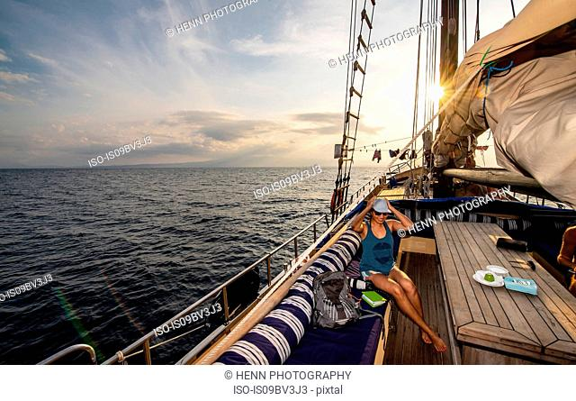 Female tourist in sunglasses and baseball cap on board sailboat, Komodo Island, East Nusa Tenggara, Indonesia