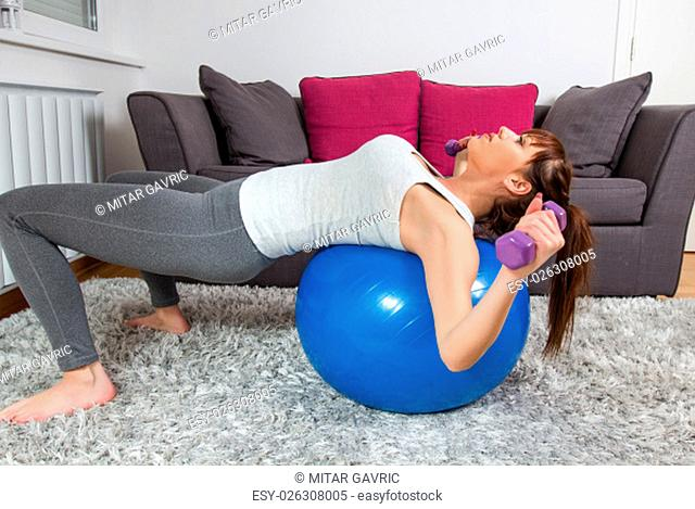 Fitness young woman, exercising with dumbbels and pilates ball at home