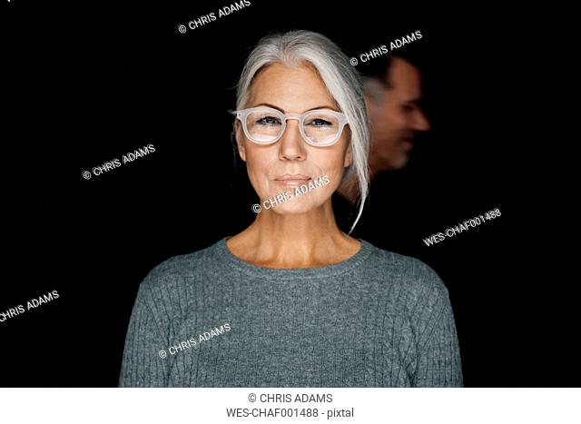 Portrait of smirking woman wearing glasses in front of black background