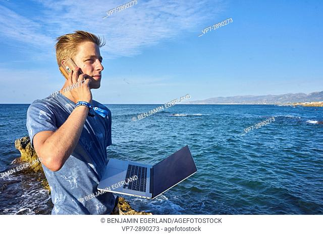 confident young man using mobile phone and laptop computer next to sea in holiday location Hersonissos, Crete, Greece
