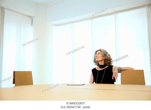 Senior female designer gazing up from boardroom table