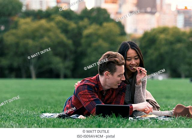 Mid adult couple eating snacks on picnic blanket in Central Park, New York, USA