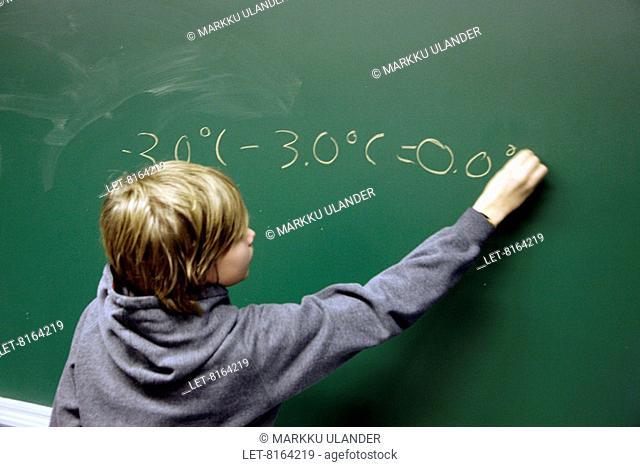School kid making calculations on a blackboard