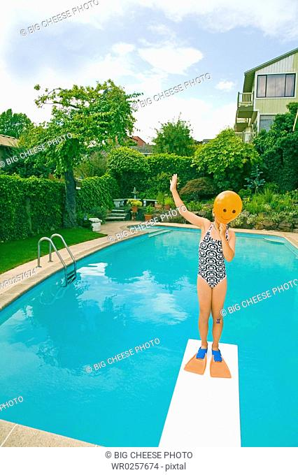 Girl with balloon in front of face over swimming pool