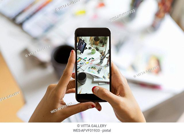 Illustrator's hands taking photo of work desk in atelier with smartphone, close-up