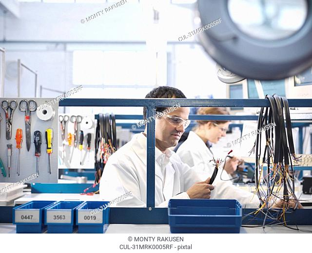 Workers making wiring loom cables