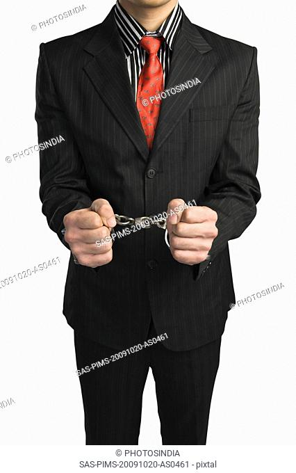 Close-up of a businessman tied up with handcuffs
