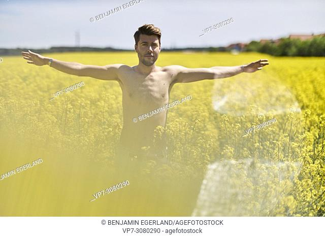 Shirtless man standing in colza field, stretching arms. Germany, Bavaria