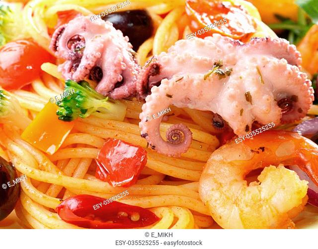 Seafood spaghetti marinara pasta with octopus, shrimps, cherry tomatoes and olives