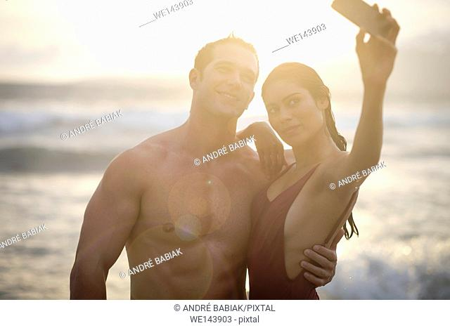 Young attractive man and woman are taking a selfie photo at the beach around sunset
