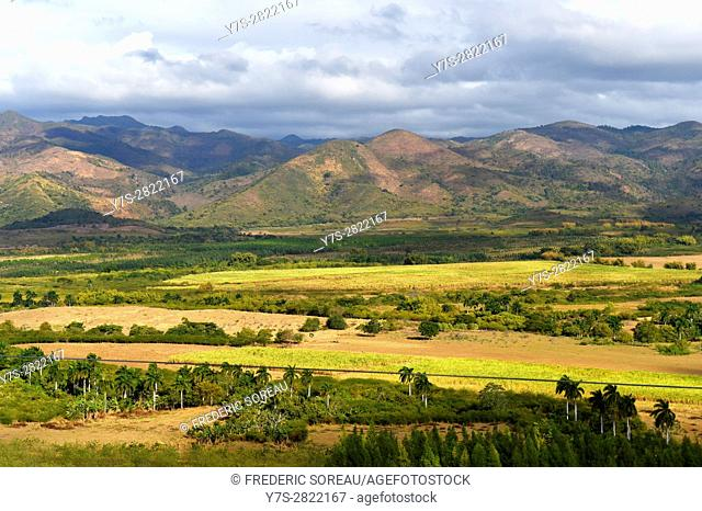 Mountains and valley with palm trees and fields in a pastoral scene outside Trinidad, Cuba