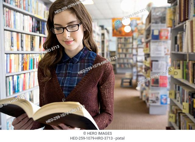 Woman reading book in aisle of bookstore