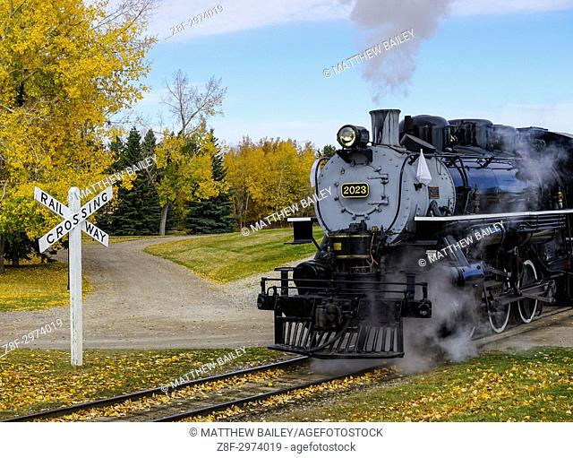 An old steam train propels down the track at Calgary Heritage Park