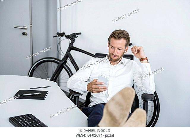 Businessman with earphones sitting at desk with feet up looking at cell phone