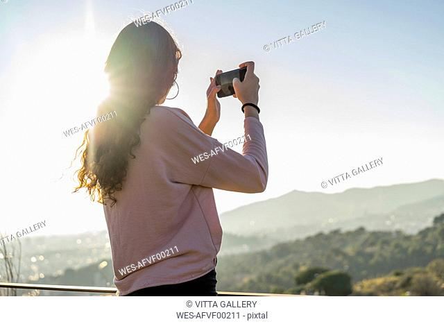 Young woman standing on a hill taking cell phone picture