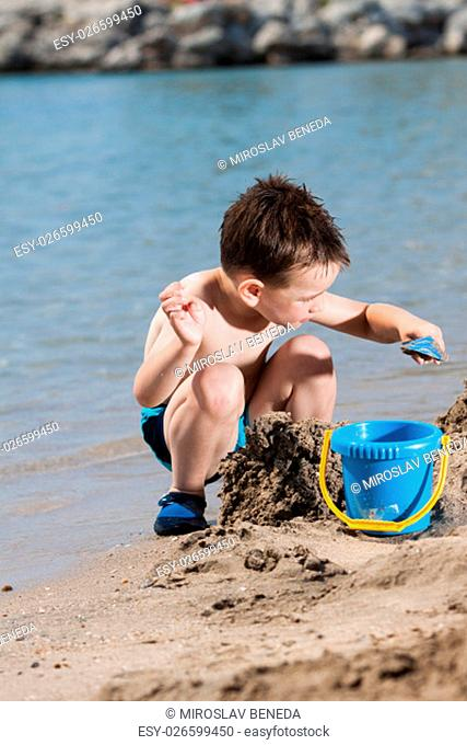 little boy in blue sea playing with mud pies and sand