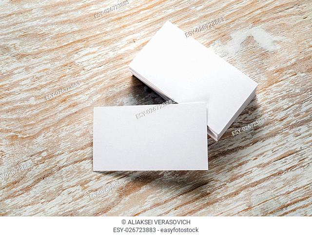 Photo of blank business cards with soft shadows on light wooden background. Mock-up for branding identity