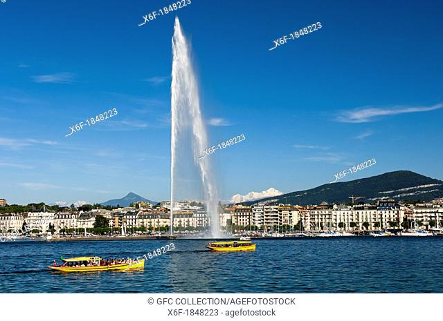 Yellow ferry boats of the company 'Mouettes Genevoises' on Lake Geneva passing by the monumental water fountain Jet d'Eau