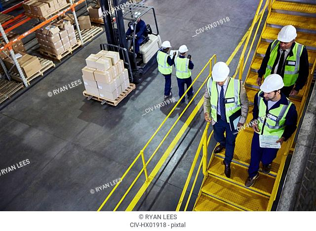 Forklift, managers and workers in distribution warehouse