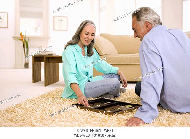 Mature couple playing backgammon in living room