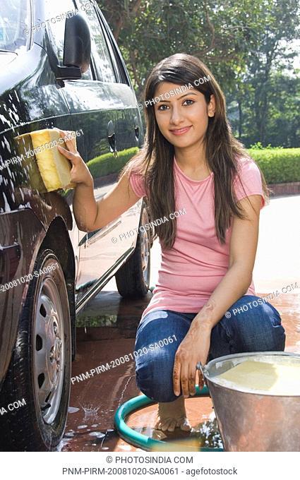 Woman washing a car and smiling, New Delhi, India