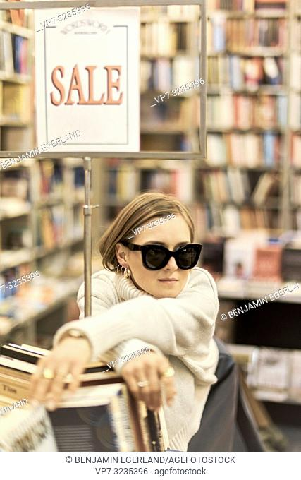 fashionable German blogger woman next to sales sign