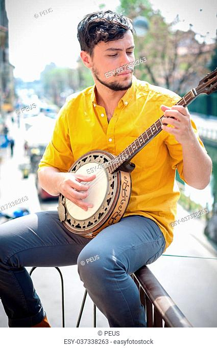 hipster young man playing banjo in the city