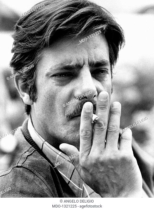 Giancarlo Giannini smoking a cigarette. The Italian actor and voice actor Giancarlo Giannini smoking a cigarette. Cannes, 1970s