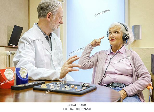 Senior patient wearing headphones talking to Audiologist during ear exam at doctor's office