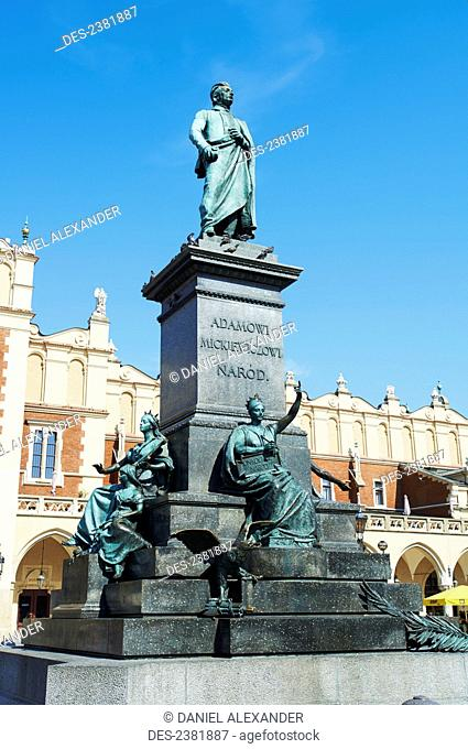 Statue of Adam Mickiewicz in Rynek Glowny in front of old cloth guild; Krakow, Poland