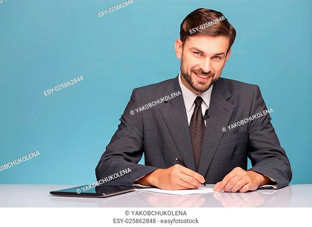 Cheerful newscaster is sitting in studio and writing. He is smiling and looking forward happily. A man is wearing a suit. Isolated on blue background