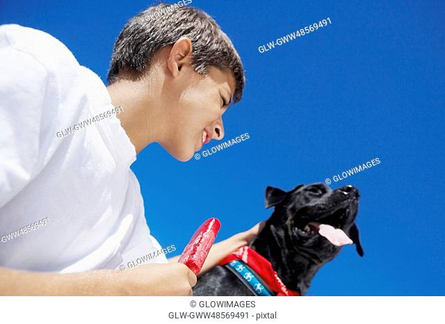 Low angle view of a boy holding an ice-cream with a dog beside him