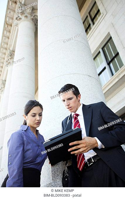 Caucasian business people looking at digital tablet