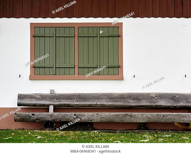 view to a house wall with a closed window and a wooden bench