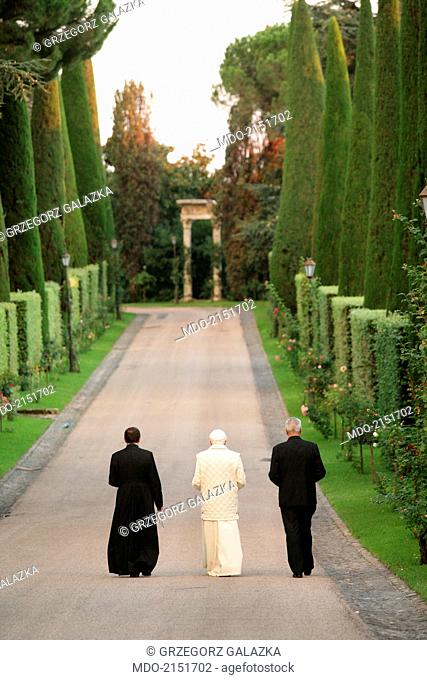 The pope Benedict XVI (Joseph Aloisius Ratzinger) walking in the garden and saying the rosary with the archbishop Mieczyslaw Mokrzycki and the butler Angelo...