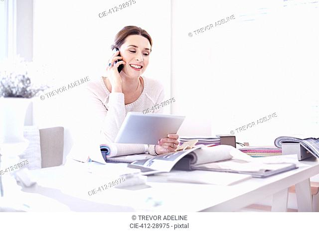Interior designer talking on cell phone and using digital tablet in office with swatches