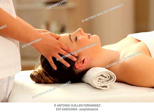 Side view portrait of a woman relaxing receiving a facial massage in a spa salon